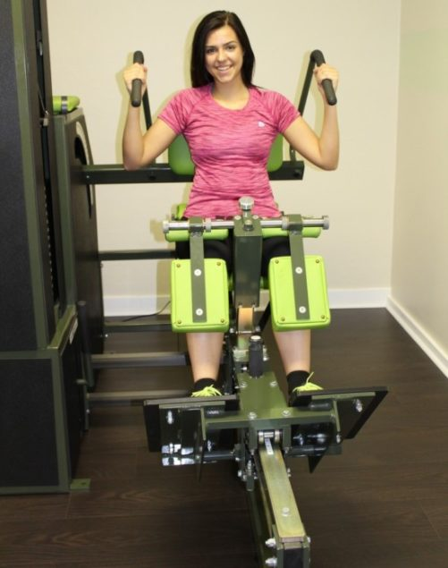 Personal trainer Megan Barnes demonstrates the equipment that focuses on lower back strengthening.